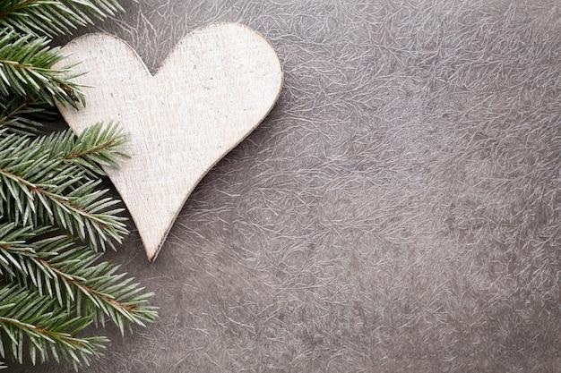 Еловая ветка с рождественскими украшениями на сером фоне.