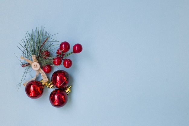 Spruce branch with rowan berries on a blue background. scenery for the holiday of christmas.