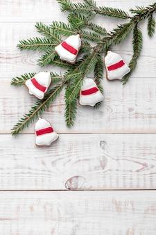 Колокольчик в форме еловых веток и печенья с красной глазурью на белом деревянном фоне с копией пространства