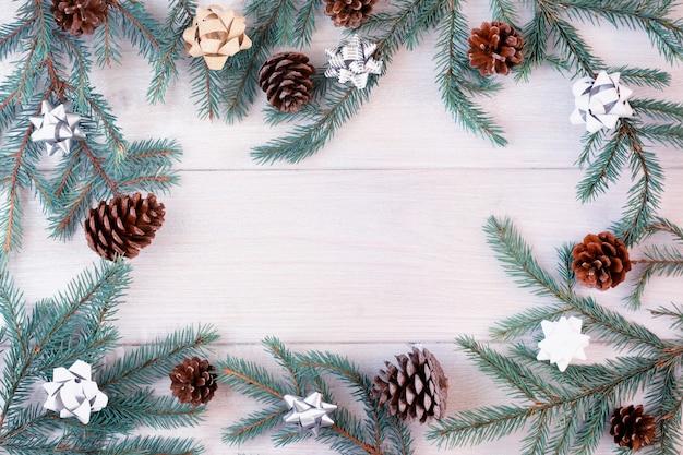 금색과 은색 활과 콘으로 장식 된 가문비 나무 가지가 밝은 나무 배경에 원으로 배열됩니다.