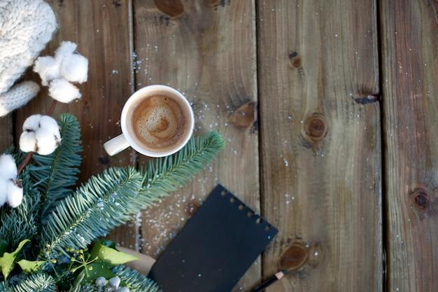 木製のコーヒーマグカップと黒いメモ帳と鉛筆と白いミトンの茶色の紙の小ぎれいなな枝