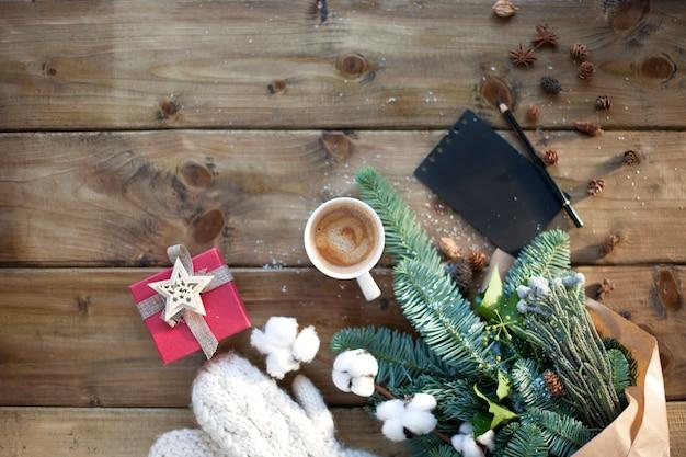 木製のコーヒーマグカップと黒いメモ帳と鉛筆の茶色の紙の小ぎれいなな枝