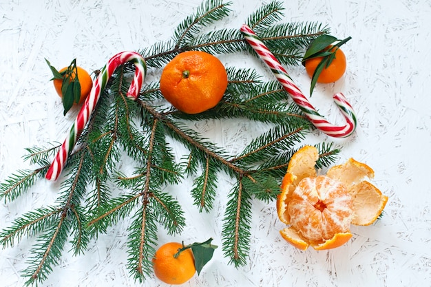 Spruce branches, tangerines, candies on a white background. view above. new year's and chr
