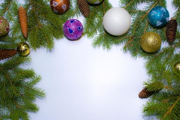 Еловые ветки с шишками и рождественскими украшениями на белом фоне с пространством для текста