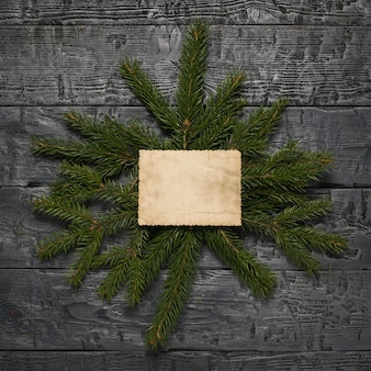 Spruce branches with a sheet of old paper on a wooden table.