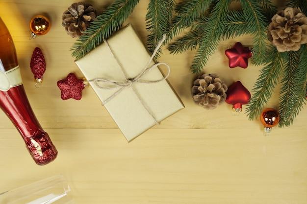 Ель, бутылка шампанского, подарок и бокалы на белом фоне деревянный стол