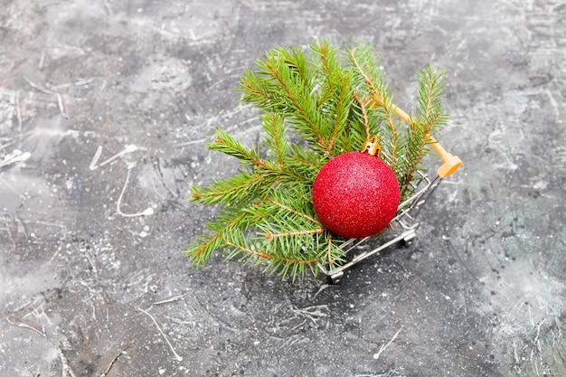 黒の背景、コピースペースのミニチュアショッピングトロリーのトウヒの緑の枝と赤い光沢のあるクリスマスツリーのおもちゃのボール