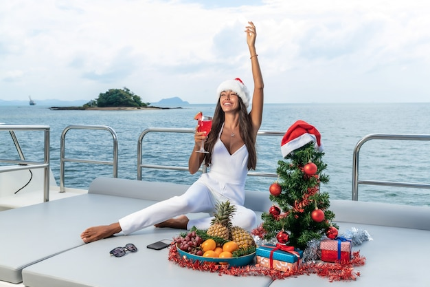 Spruce on a yacht. new year on the islands. an attractive lady celebrates christmas in a santa hat on a yacht.