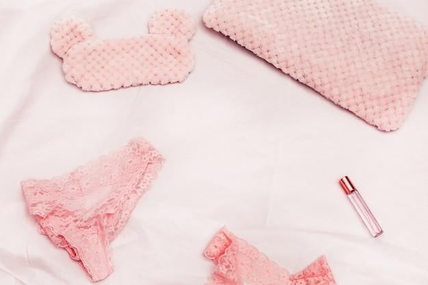 レースの下着、睡眠マスク、白い綿のシートに香水のセット。女性のためのアクセサリー。ロマンスのライフスタイルとピンクの夢。トップビューとspsceをコピーします。