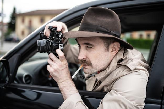 Фотограф-шпион или папарацци, детектив, использующий камеру в своей машине