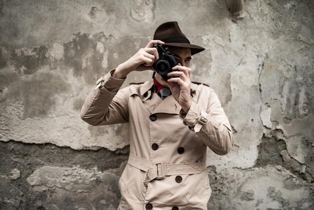 Шпион или фотограф папарацци, человек, использующий камеру на городской улице