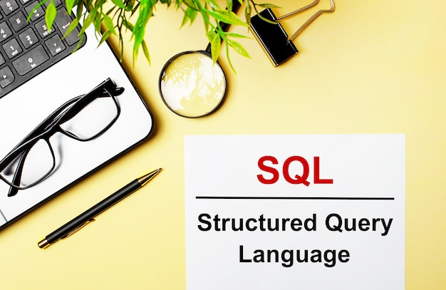 Sql structured query language is written in red on a white piece of paper on a light yellow background next to a laptop, pen, magnifying glass, glasses and a green plant.