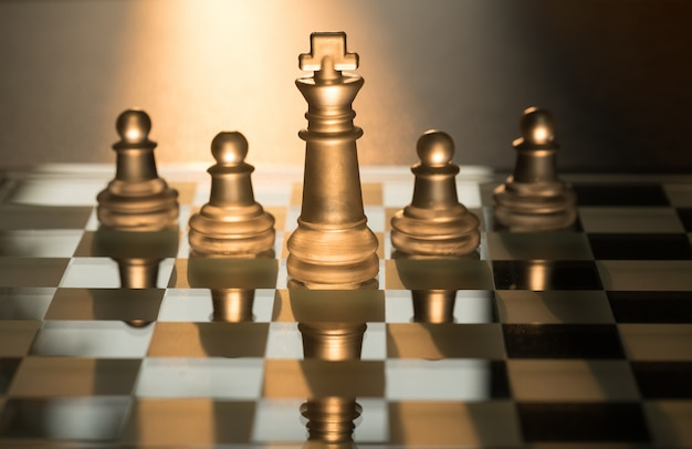 Squad of 5 chess pieces leaded by the king with sun light background.