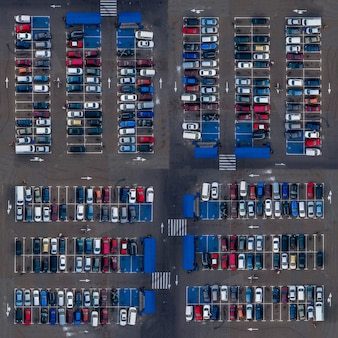 Square aerial top view parking lot cars. parking lot top view cars are parked in open parking near market places. Premium Photo