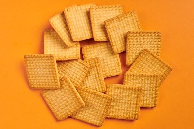 正方形のビスケット、オレンジ色の背景。美味しいおやつ。四角いクッキー。