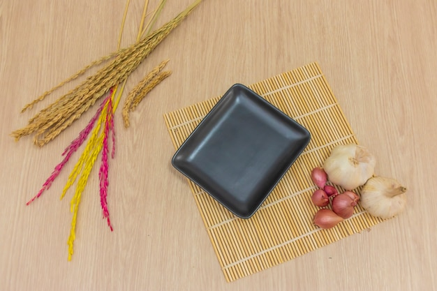 A square black plate was placed on the table and garlic rice, onions were placed around it.