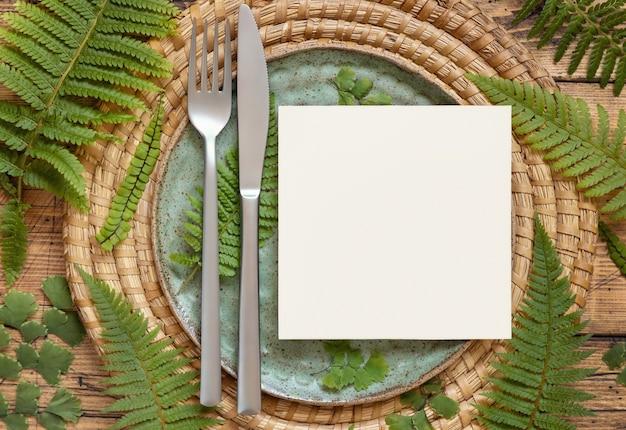Квадратная пустая бумажная карточка на сервировке стола, украшенной листьями папоротника на деревянном столе. тропический макет сцены с плоской планировкой пригласительного билета
