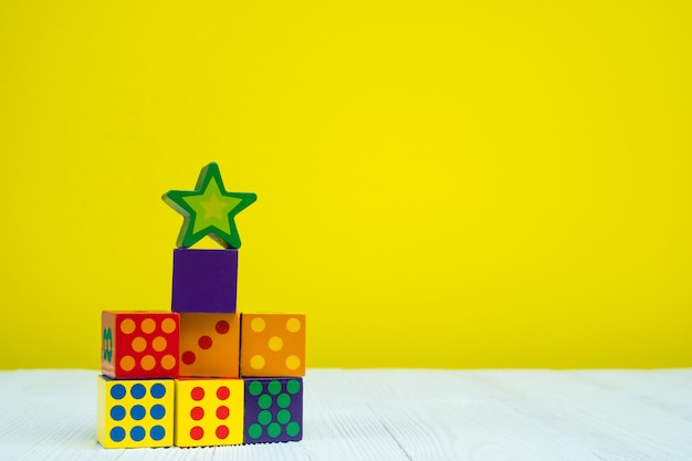 Square block puzzle toy on table with yellow