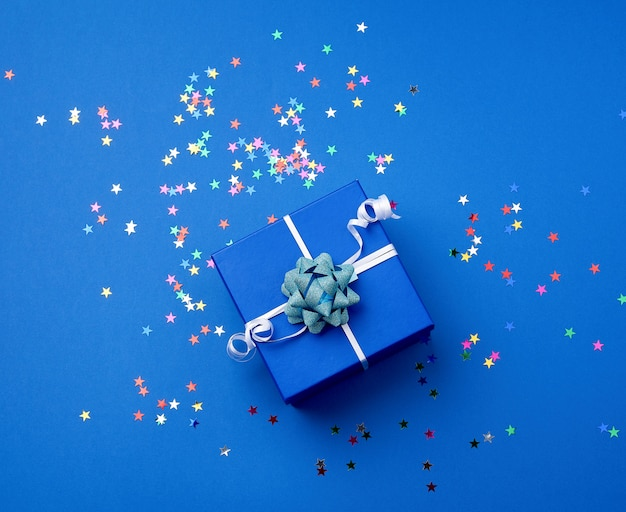 Square blue  box with a bow and multicolored sparkles