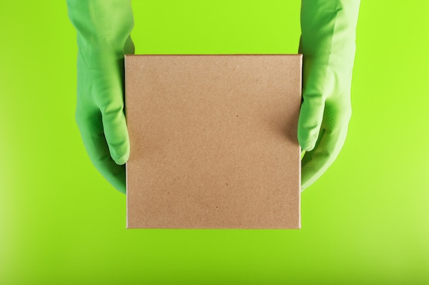 A square box in the hands with green rubber gloves on a green background.