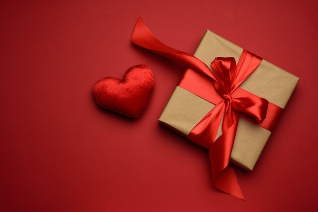 Square box with red silk bow and textile heart  on red background, top view, valentine's day
