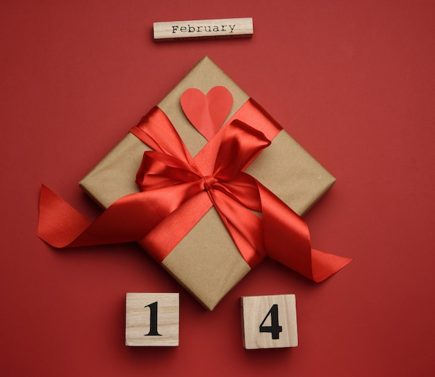 Square box with red silk bow and wooden calendar with date 14 february on red background, top view, valentine's day