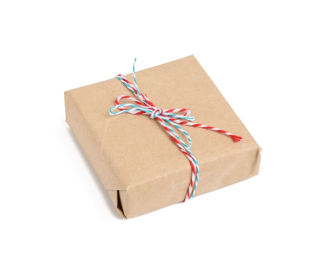 Square box wrapped in brown kraft paper and tied with red rope, gift isolated on white