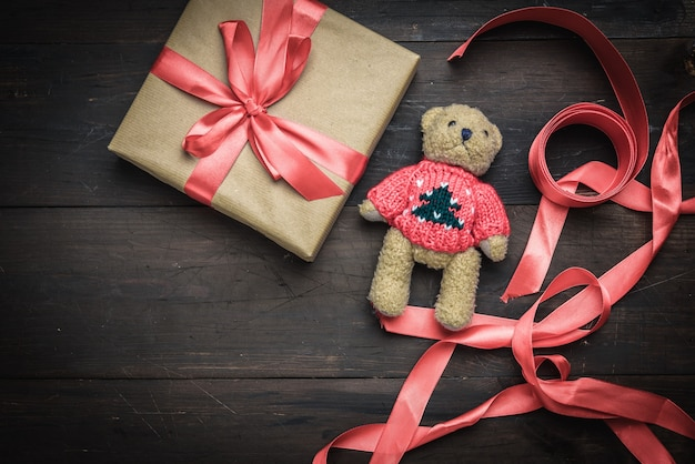 Square box wrapped in brown kraft paper and tied with red silk ribbon on brown wooden table with teddy bear