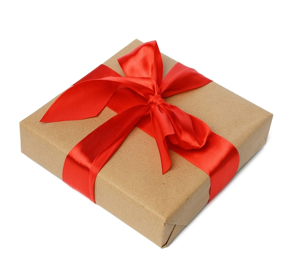 Square box wrapped in brown kraft paper and tied with red silk ribbon, gift isolated on white background