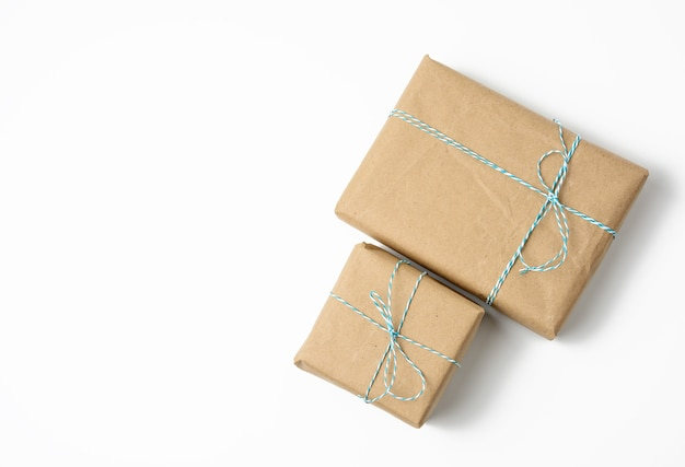 Square box wrapped in brown kraft paper and tied with rope, gift on white background, copy space