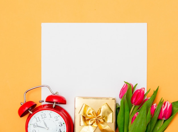 黄色のギフトボックスと目覚まし時計付きの正方形の段ボールとチューリップ