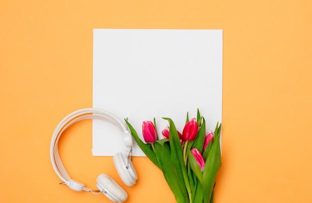 Квадратный картон и тюльпаны с наушниками на желтом