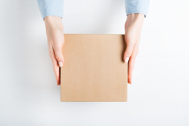 Square cardboard box in female hands.