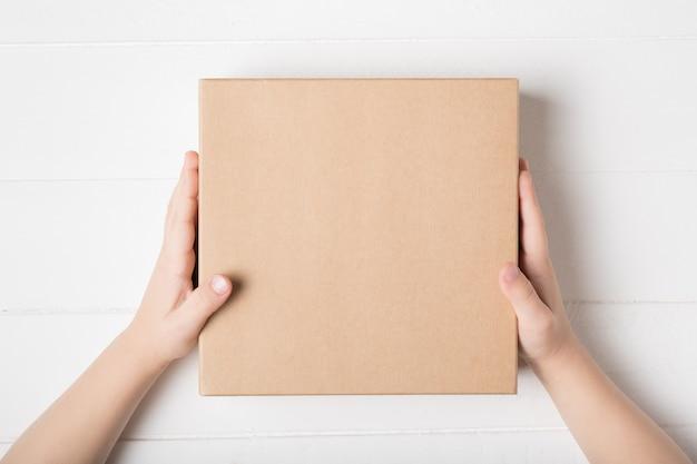 어린이 손에 사각형 골 판지 상자입니다. 상위 뷰, 흰색 배경
