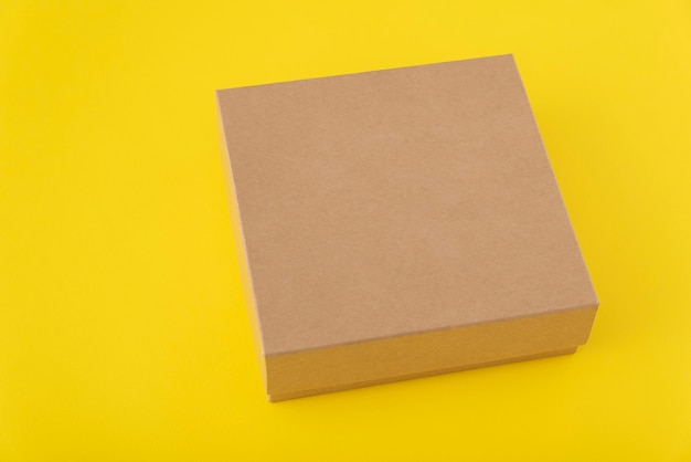 黄色の背景に正方形の段ボール箱。スペースをコピーします。モックアップ