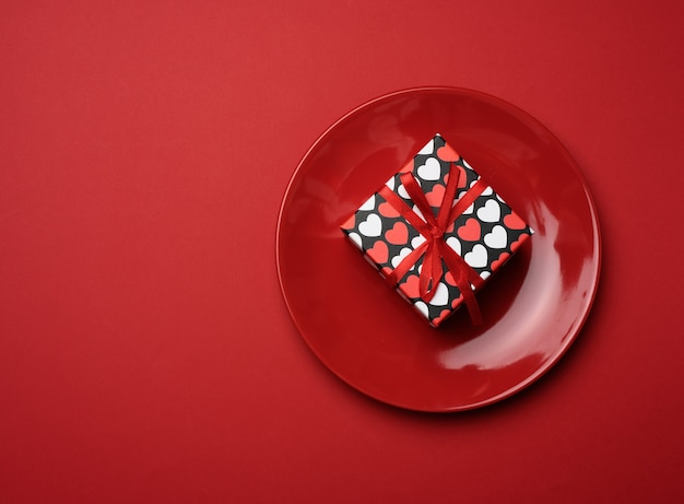 Square cardboard box tied with a silk red ribbon lies in a round ceramic red plate, top view, copy space