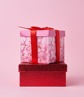 Square cardboard pink box tied with a red bow on a pink background
