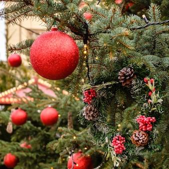 Квадратная рождественская открытка. крупным планом красные новогодние шары и гирлянды на ветвях натуральной рождественской елки на открытом воздухе в солнечный летний день. ни людей, ни снега.