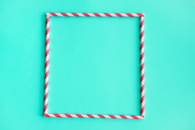 Square of colored, striped straws for drinking juice or cocktail on green.