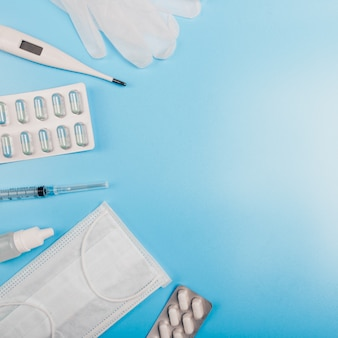 Квадратный состав с медицинской маской, термометр, шприц, таблетки и перчатки на синем фоне. copyspace.