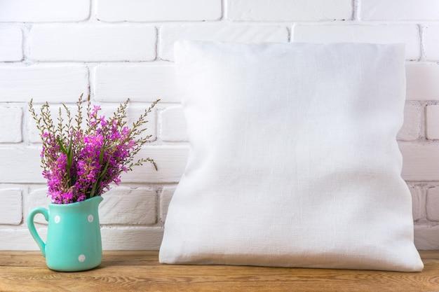 Мокап квадратной хлопковой подушки с пурпурными полевыми цветами в мятном кувшине в горошек