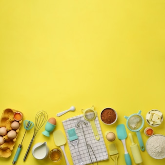 Square crop. baking ingredients - butter, sugar, flour, eggs, oil, spoon, rolling pin, brush, whisk, towel over yellow background.