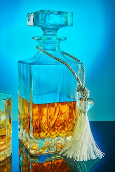 Square crystal decanter with scotch whiskey or brandy on a blue gradient background with reflection