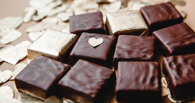 Квадратные темные шоколадные конфеты и вырезанные из фольги сердца крупным планом на столе