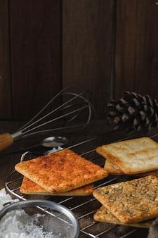 木製のテーブルの上の正方形のドライクラッカービスケット木製のテクスチャ暗い背景スナックドライビスケット