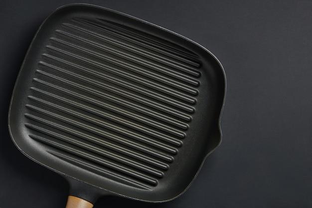 검은 테이블 배경에 사각형 빈 프라이팬입니다. 고기나 야채를 굽기 위한 철판 도구. 텍스트 복사 공간이 있는 상위 뷰입니다.