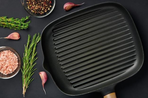 향신료와 조미료와 함께 검은 테이블 배경에 사각 빈 프라이팬. 고기나 야채를 굽기 위한 철판 도구. 텍스트 복사 공간이 있는 상위 뷰입니다.