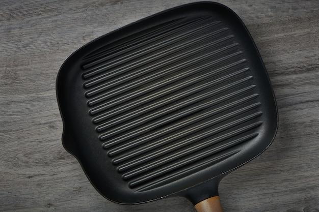 나무 테이블 배경에 사각형 빈 프라이팬입니다. 고기나 야채를 굽기 위한 철판 도구. 텍스트 복사 공간이 있는 상위 뷰입니다.