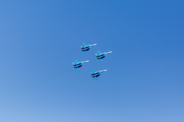 A square formation of a group of four russian military fighter jet planes flying high in blue sky
