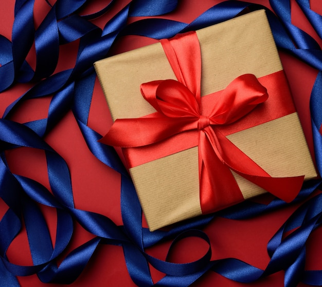 Square gift box is packed in brown paper and curled blue silk ribbon on a red background, festive background, top view